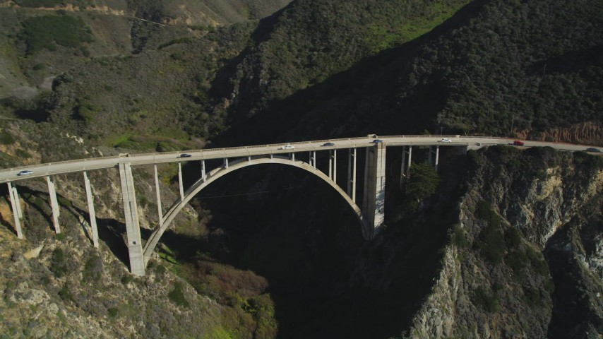 5K stock footage aerial video of flying away from Bixby Creek Bridge above coastal cliffs, Big Sur, California Aerial Stock Footage | DFKSF16_076