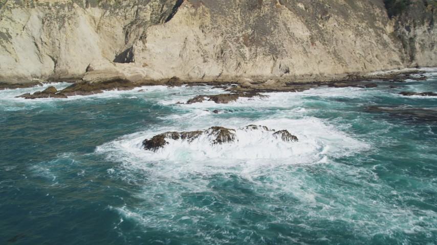 5K stock footage aerial video of passing ocean rock formations near coastal cliffs, Big Sur, California Aerial Stock Footage | DFKSF16_086