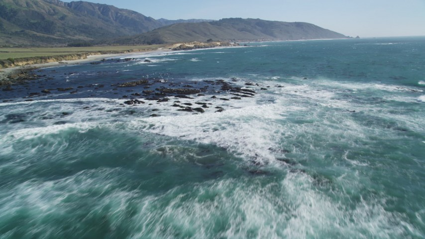 5K aerial video tilt from ocean, reveal seagulls flying over rocks along coast, Big Sur, California Aerial Stock Footage | DFKSF16_095