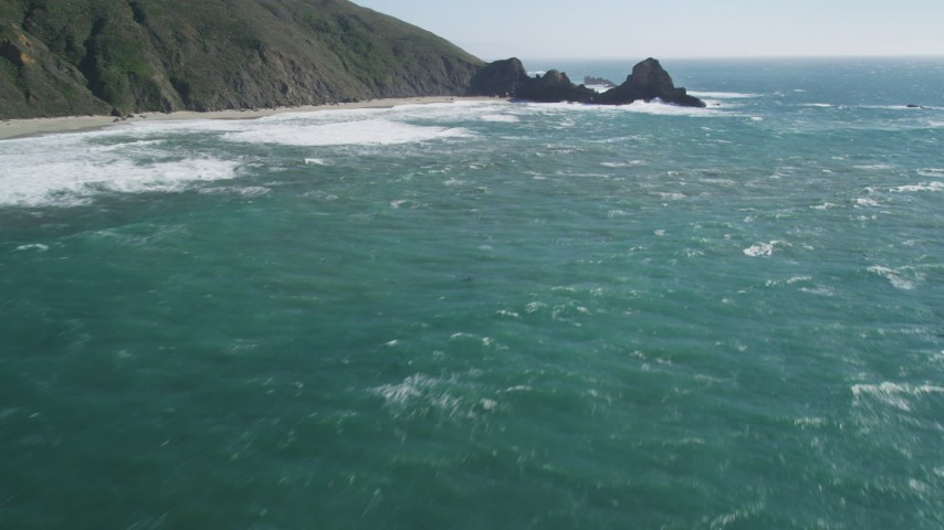 5K aerial video of tilting up from the ocean to reveal coastal cliffs and rock formations, Big Sur, California Aerial Stock Footage | DFKSF16_100