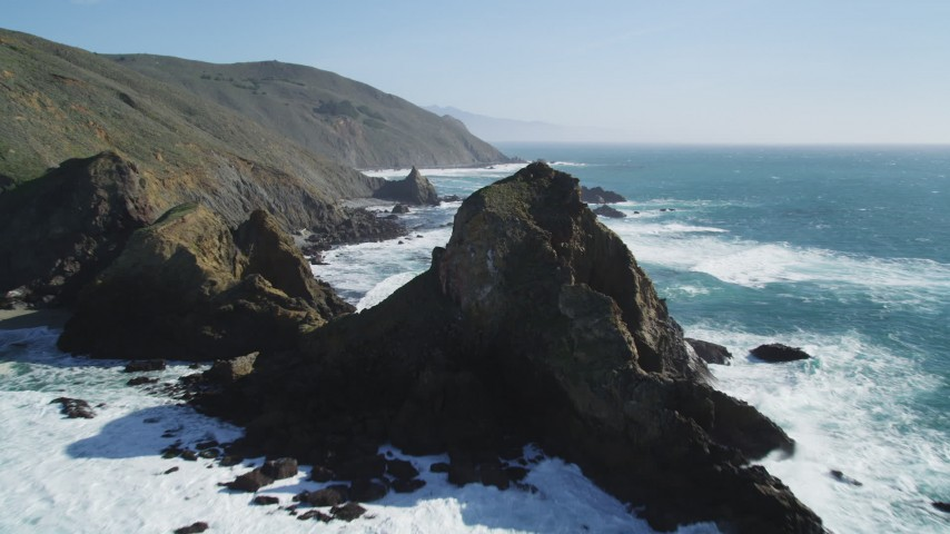 5K aerial video tilt from the ocean to reveal coastal rock formations and cliffs, Big Sur, California Aerial Stock Footage | DFKSF16_101