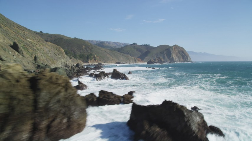 5K stock footage aerial video tilt from ocean to reveal coastal rock formations below cliffs, Big Sur, California Aerial Stock Footage | DFKSF16_103