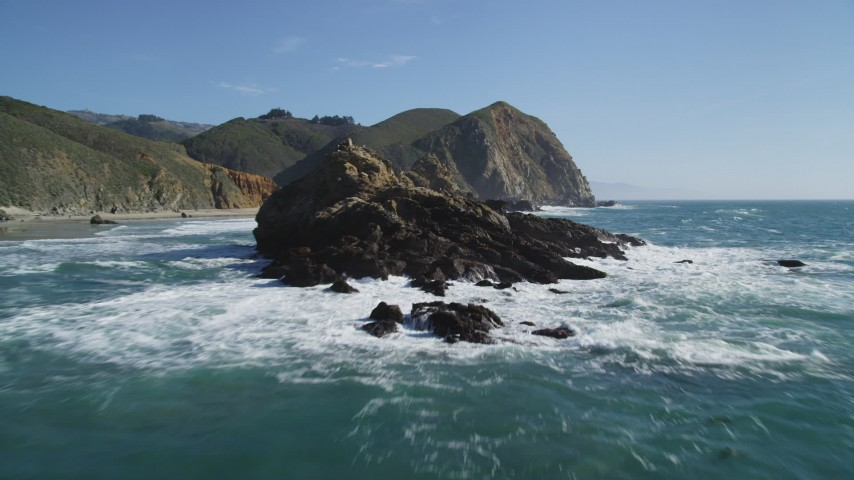 5K aerial video tilt from the ocean to reveal rock formations near coastal cliffs, Big Sur, California Aerial Stock Footage | DFKSF16_104