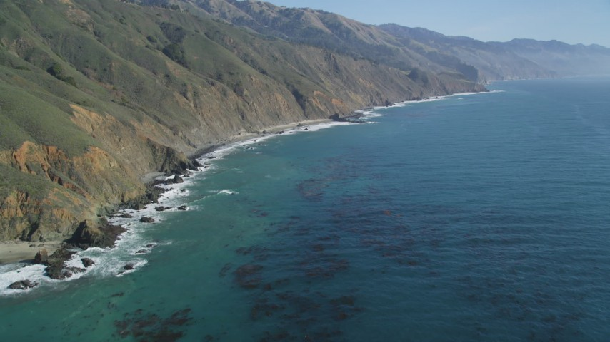 5K aerial video of flying over the ocean, tilt up to reveal coastal cliffs, Big Sur, California Aerial Stock Footage | DFKSF16_108