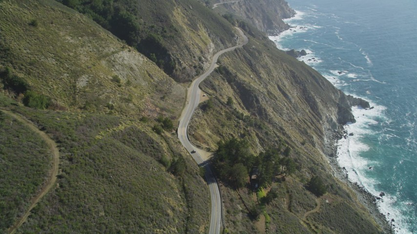 5K aerial video of flying over the Highway 1 road atop coastal cliffs, tilt to cars, Big Sur, California Aerial Stock Footage DFKSF16_116