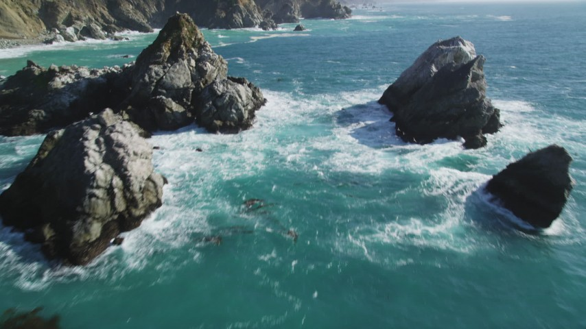 5K aerial video of flying between large rock formations, tilt revealing coastal cliffs, Big Sur, California Aerial Stock Footage | DFKSF16_122