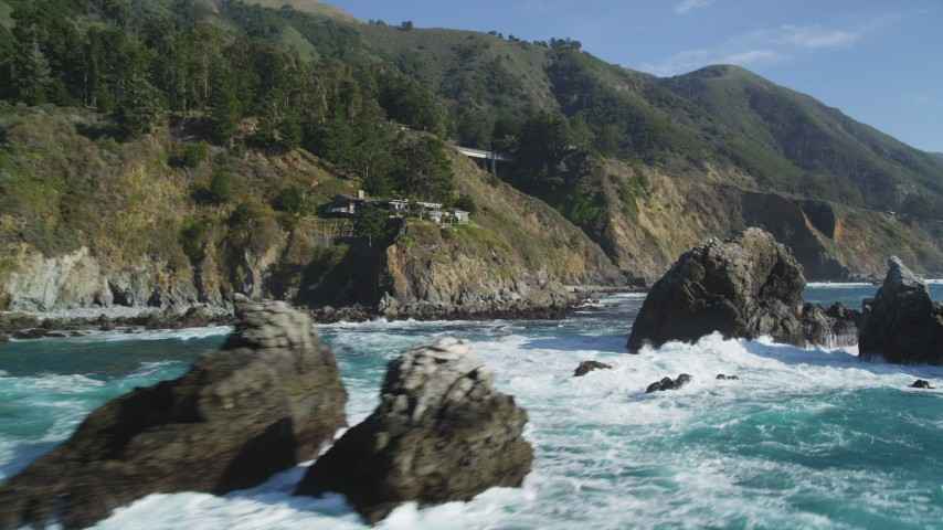 5K aerial video tilt from the ocean to reveal rock formations, home atop coastal cliff, Big Sur, California Aerial Stock Footage | DFKSF16_125