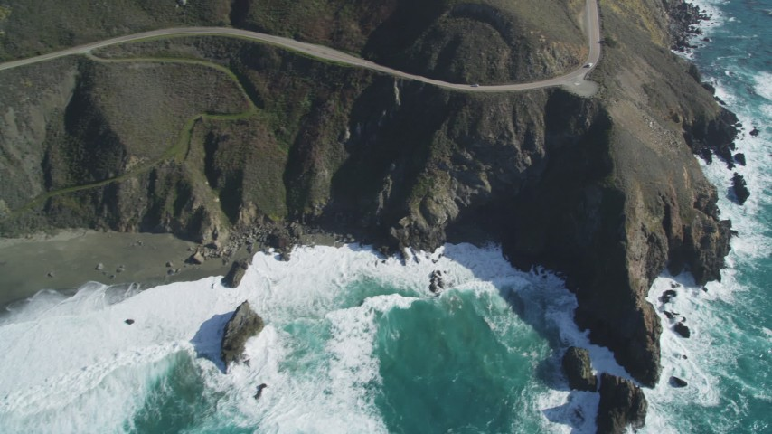 5K aerial video of flying by small beach, pan right to Highway 1 atop coastal cliffs, Big Sur, California Aerial Stock Footage | DFKSF16_129