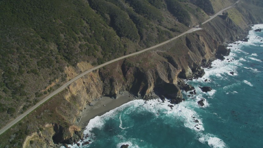 5K aerial video tilt Highway 1 coastal road, small beach and coastal cliffs, Big Sur, California Aerial Stock Footage | DFKSF16_131