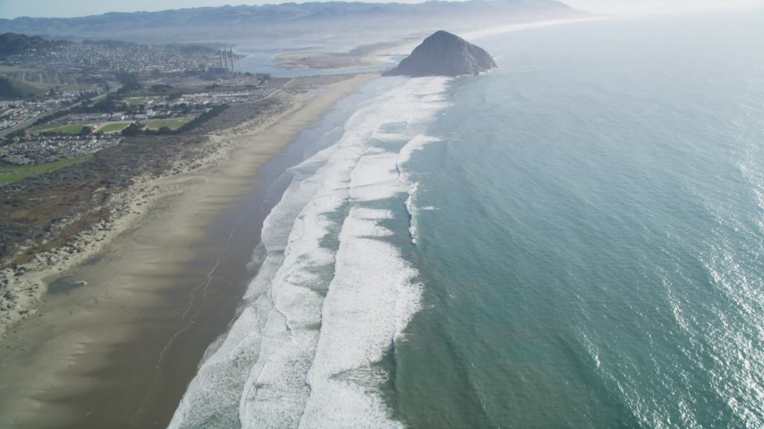 5K stock footage aerial video of tilting from Morrow Strand Beach revealing Morro Rock, Morro Bay, California Aerial Stock Footage | DFKSF16_153