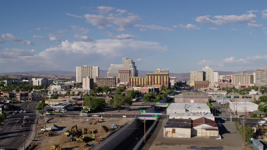 5.7K stock footage aerial video of a reverse view of train tracks leading to the city skyline in Reno, Nevada Aerial Stock Footage | DX0001_000065