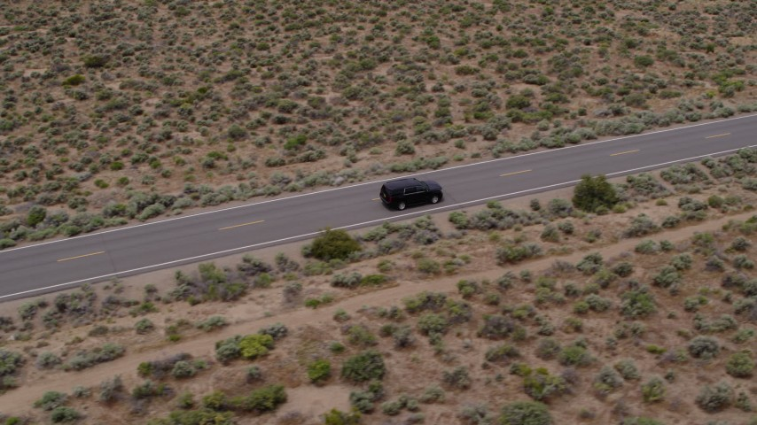 5.7K stock footage aerial video of tracking a black SUV on a desert road in Carson City, Nevada Aerial Stock Footage | DX0001_000127