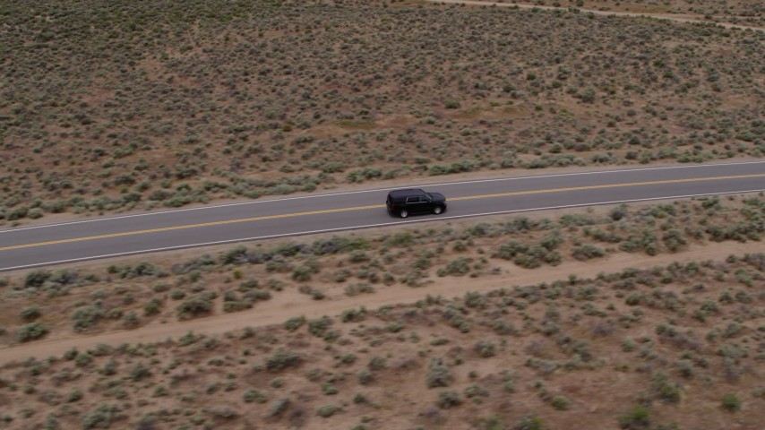 5.7K aerial video track a black SUV as it drives on a desert road in Carson City, Nevada Aerial Stock Footage | DX0001_000130