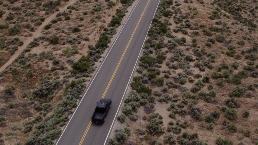 5.7K stock footage aerial video of revealing a black truck driving on a desert road in Carson City, Nevada Aerial Stock Footage | DX0001_000139