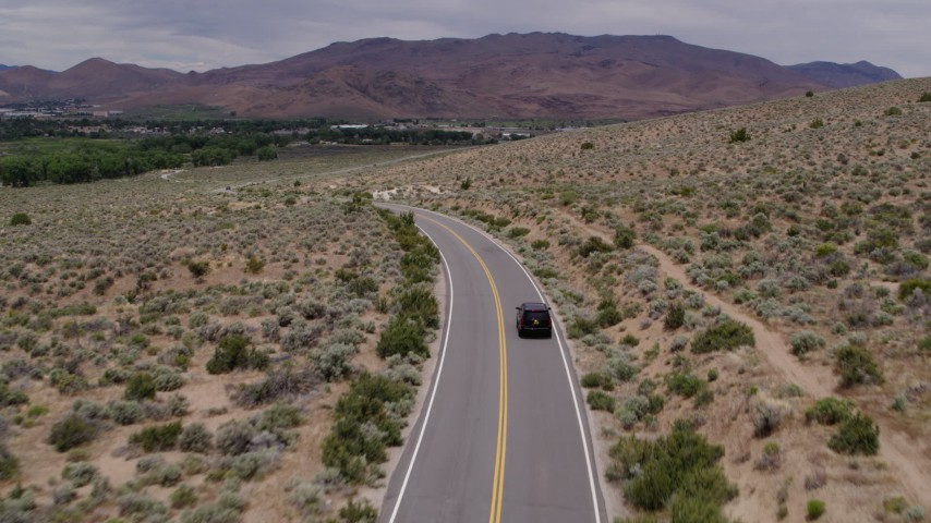 5.7K stock footage aerial video of a black SUV driving by on a desert road in Carson City, Nevada Aerial Stock Footage | DX0001_000140