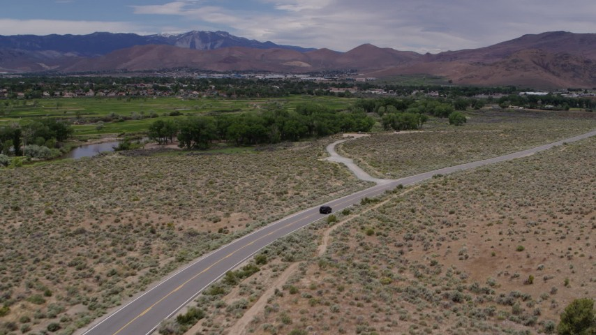 5.7K stock footage aerial video of a black SUV driving on a desert road in Carson City, Nevada Aerial Stock Footage | DX0001_000141
