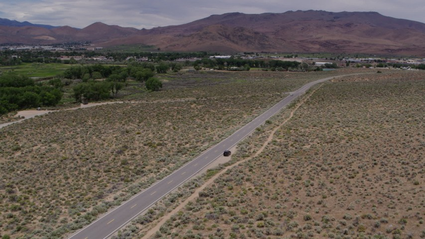 5.7K stock footage aerial video approach a black SUV driving to the side of the road in Carson City, Nevada Aerial Stock Footage | DX0001_000142