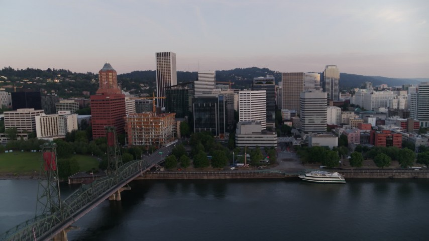 4K stock footage aerial video flying by office building and the Hawthorne Bridge at sunrise, Downtown Portland, Oregon Aerial Stock Footage | DX0001_000167