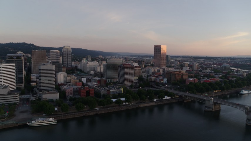 4K stock footage aerial video of downtown buildings, Morrison Bridge at sunrise, Downtown Portland, Oregon Aerial Stock Footage | DX0001_000172