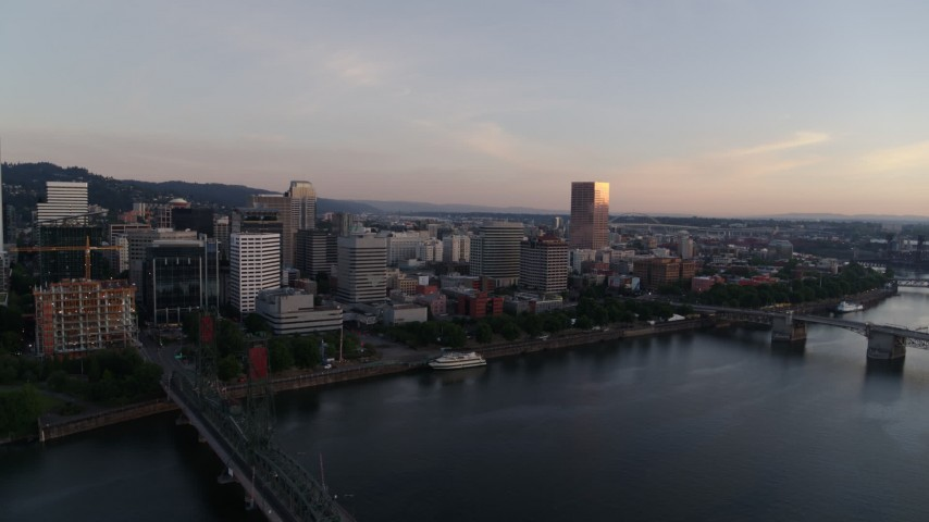 4K stock footage aerial video flying away from Morrison Bridge and over the Hawthorne Bridge at sunrise, Downtown Portland, Oregon Aerial Stock Footage | DX0001_000173