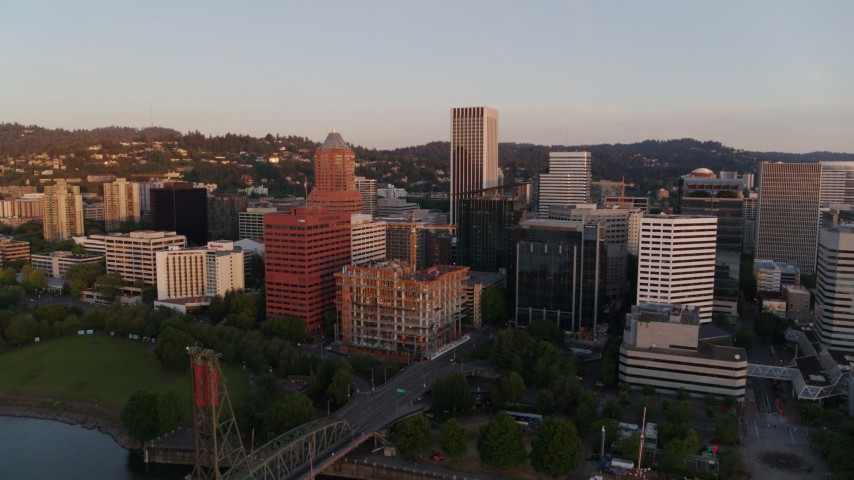 4K stock footage aerial video approaching downtown buildings, passing the Hawthorne Bridge at sunrise, Downtown Portland, Oregon Aerial Stock Footage | DX0001_000176