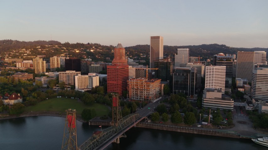 4K stock footage aerial video flying away from downtown, over the Hawthorne Bridge at sunrise, Downtown Portland, Oregon Aerial Stock Footage | DX0001_000177