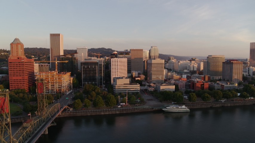 4K stock footage aerial video flying away from Downtown and toward the Hawthorne Bridge at sunrise, Downtown Portland, Oregon Aerial Stock Footage | DX0001_000181