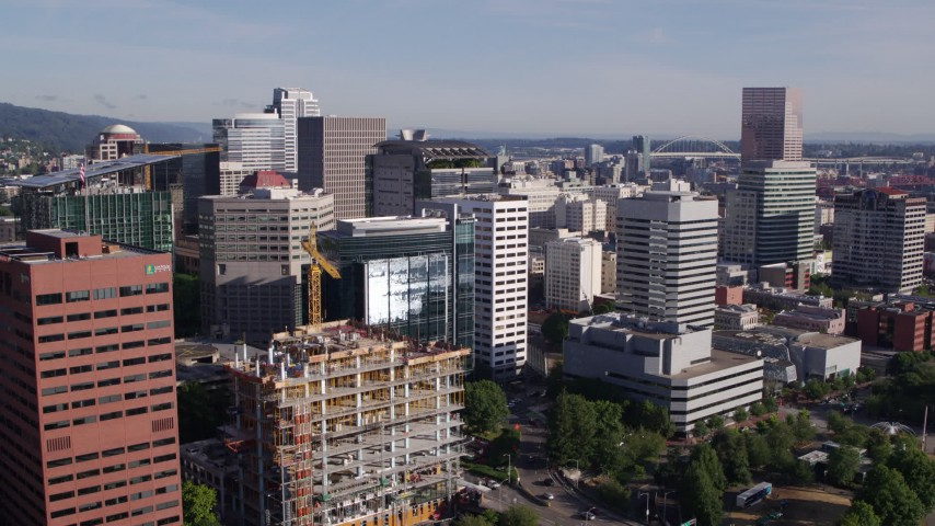 5.7K stock footage aerial video flying away from downtown buildings, skyscrapers and construction crane, Downtown Portland, Oregon Aerial Stock Footage | DX0001_000218