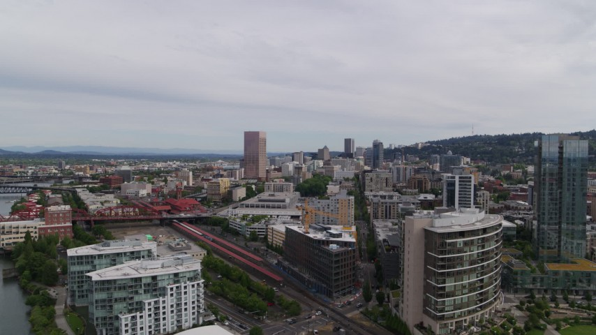 5.7K stock footage aerial video of distant skyscrapers seen from the train station and condominiums, Downtown Portland, Oregon Aerial Stock Footage | DX0001_000260