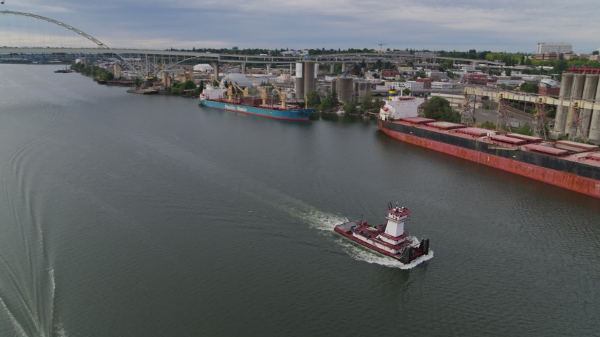 5.7K stock footage aerial video tracking a tugboat sailing past cargo ships and North Portland, Oregon Aerial Stock Footage | DX0001_000267