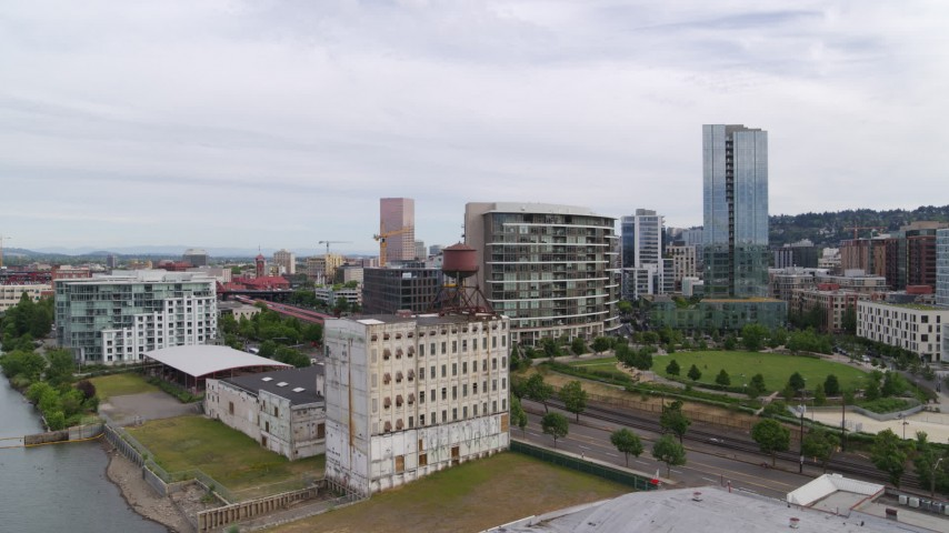 5.7K stock footage aerial video descending toward an old factory near a park, sunset, Downtown Portland, Oregon Aerial Stock Footage | DX0001_000271