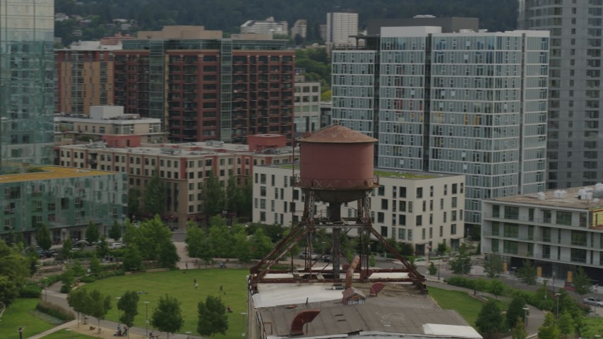 5.7K stock footage aerial video orbiting an old water tower atop a factory building, sunset, Downtown Portland, Oregon Aerial Stock Footage | DX0001_000276