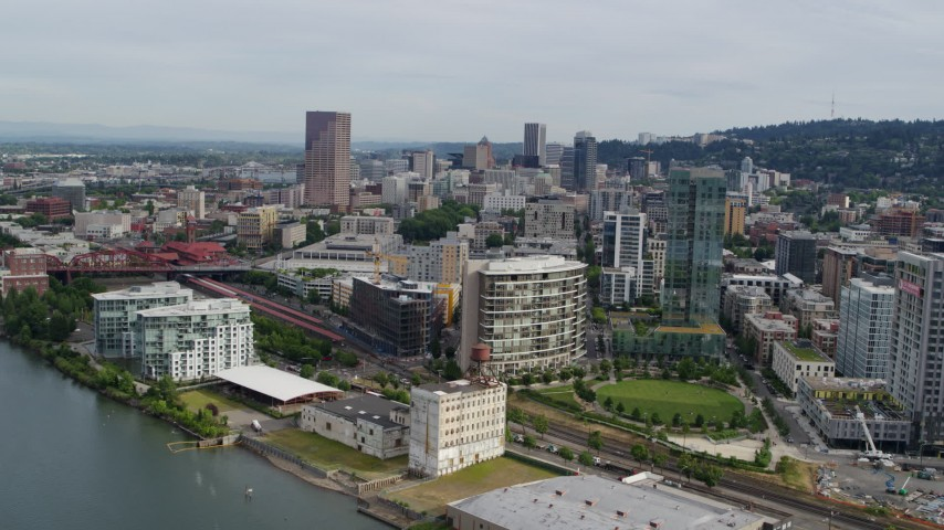 5.7K stock footage aerial video of downtown buildings, waterfront condominiums and a park, sunset, Downtown Portland, Oregon Aerial Stock Footage | DX0001_000284