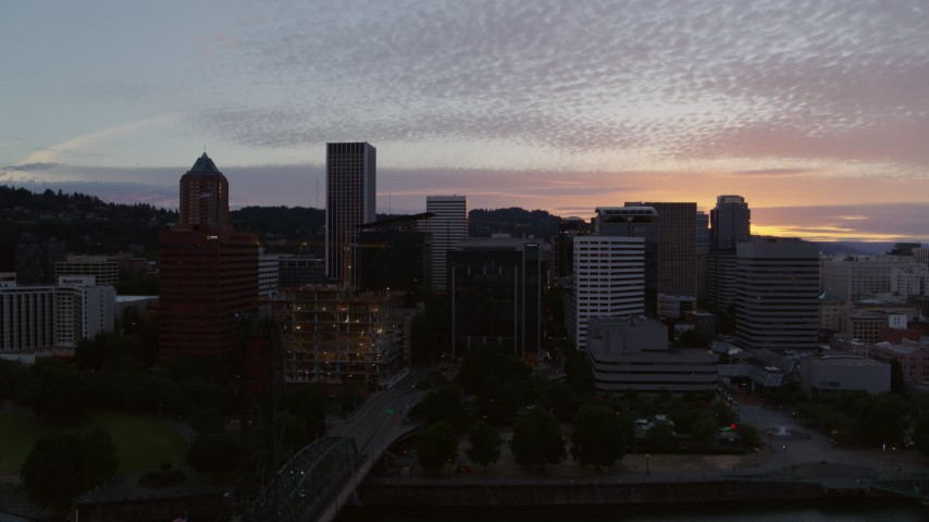 5.7K stock footage aerial video flying by a bridge with a view of Downtown Portland, Oregon at twilight Aerial Stock Footage | DX0001_000320