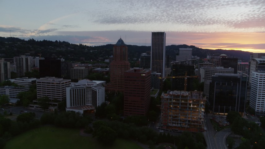 5.7K stock footage aerial video pulling back from office buildings and skyscrapers in Downtown Portland, Oregon, twilight Aerial Stock Footage | DX0001_000323