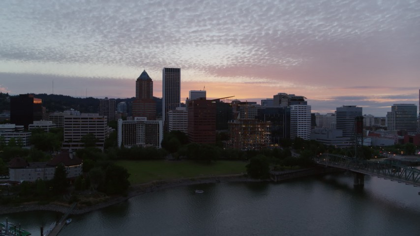 5.7K stock footage aerial video descending across the river with a view of Downtown Portland, Oregon at twilight Aerial Stock Footage | DX0001_000324
