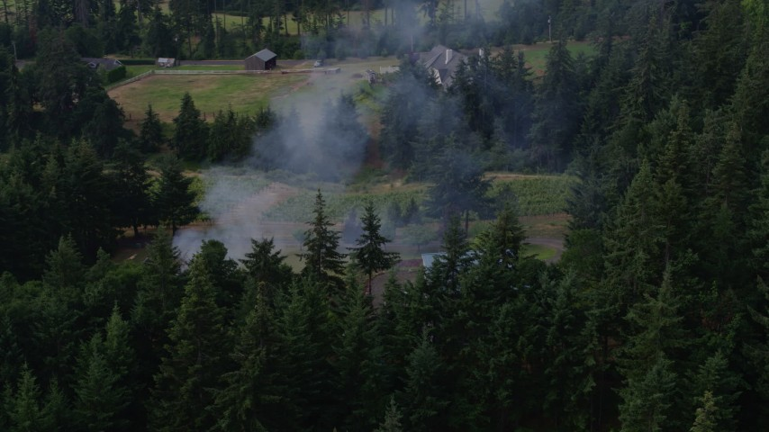 5.7K aerial video orbit a fire near rural homes in Hood River, Oregon Aerial Stock Footage | DX0001_000353