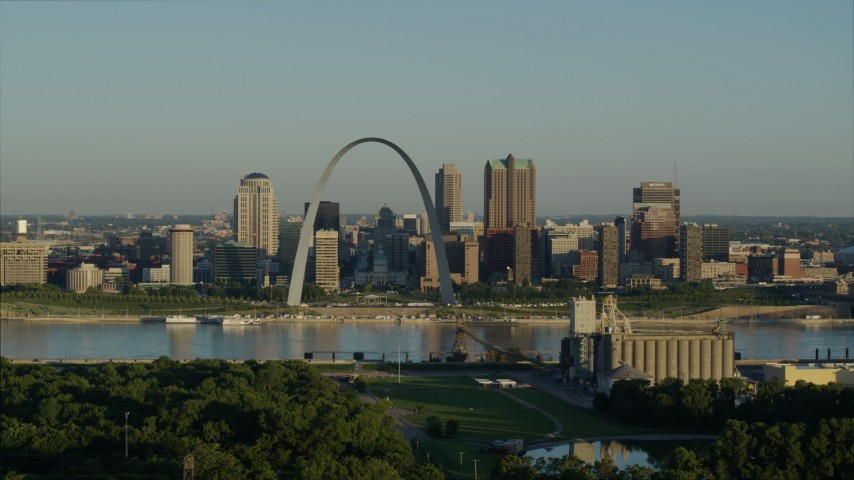 5.7K aerial video reverse shot of the Arch and skyline seen from a park across the Mississippi River, sunrise, Downtown St. Louis, Missouri Aerial Stock Footage | DX0001_000520
