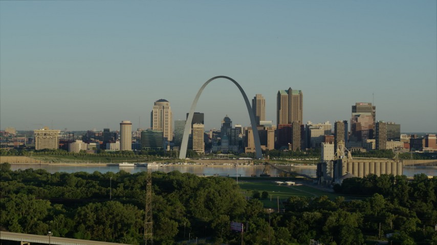 5.7K stock footage aerial video ascending over park toward Mississippi River, Arch and skyline at sunrise, Downtown St. Louis, Missouri Aerial Stock Footage | DX0001_000523