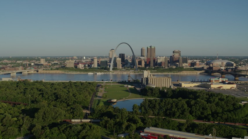 5.7K aerial video of a park and St. Louis skyline seen from across Mississippi River, sunrise, Downtown St. Louis, Missouri Aerial Stock Footage | DX0001_000534