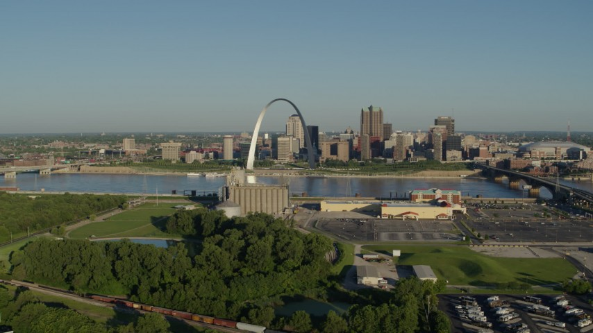 5.7K stock footage aerial video of a park and factory along the river with views of the Arch and skyline, sunrise, Downtown St. Louis, Missouri Aerial Stock Footage | DX0001_000536
