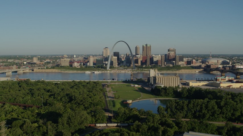 5.7K stock footage aerial video of skyline and Arch seen from a park along the river at sunrise, Downtown St. Louis, Missouri Aerial Stock Footage | DX0001_000542