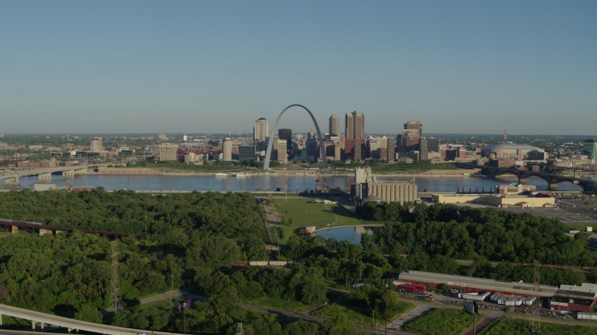5.7K aerial video reverse over freeway and park showcasing skyline and Arch, sunrise, Downtown St. Louis, Missouri Aerial Stock Footage | DX0001_000548