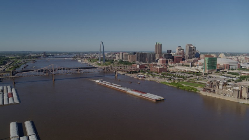5.7K aerial video of barges in the river near the Gateway Arch in Downtown St. Louis, Missouri Aerial Stock Footage | DX0001_000576