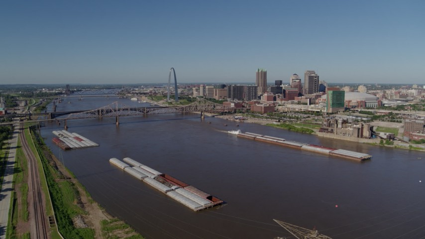 5.7K aerial video side view of Mississippi River and barges with city in the distance, Downtown St. Louis, Missouri Aerial Stock Footage | DX0001_000580