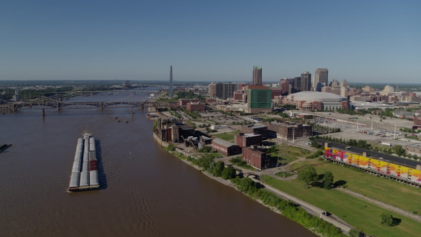 5.7K aerial video flyby riverfront buildings and river barge in Downtown St. Louis, Missouri Aerial Stock Footage | DX0001_000583
