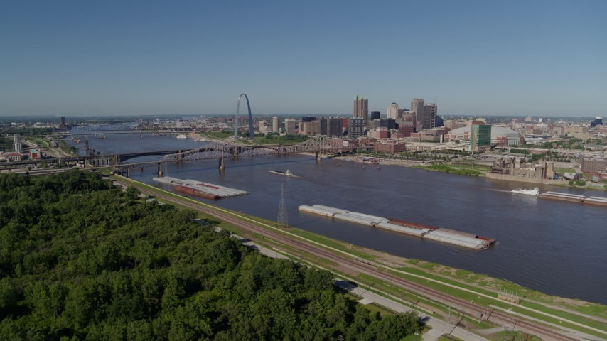 5.7K aerial video flyby barges on the river and over trees, Downtown St. Louis, Missouri Aerial Stock Footage | DX0001_000585