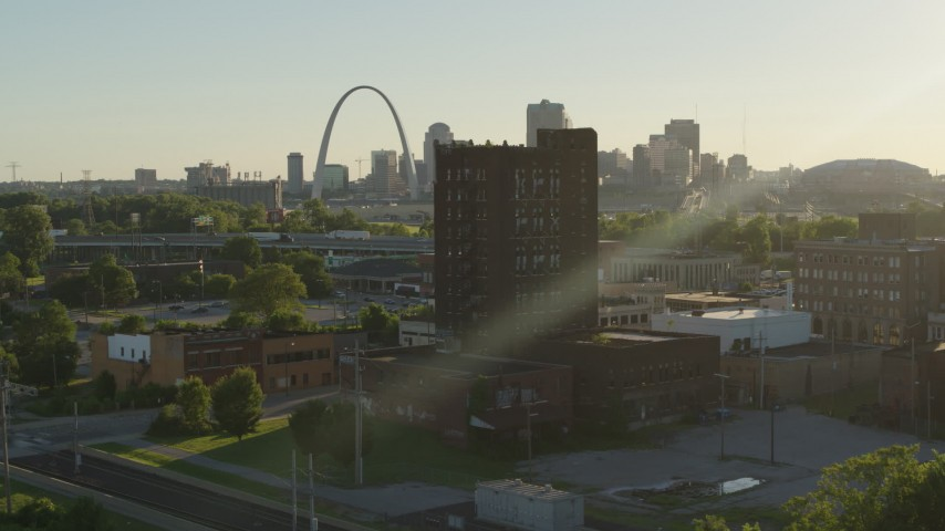 5.7K stock footage aerial video approach a brick building at sunset in East St. Louis, Illinois with the Gateway Arch in background Aerial Stock Footage | DX0001_000678