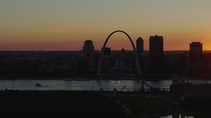 5.7K stock footage aerial video of the Gateway Arch and Downtown St. Louis, Missouri skyline in silhouette at sunset Aerial Stock Footage | DX0001_000726