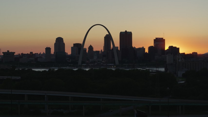 5.7K stock footage aerial video ascend and approach the Gateway Arch and Downtown St. Louis, Missouri skyline in silhouette at sunset Aerial Stock Footage | DX0001_000728